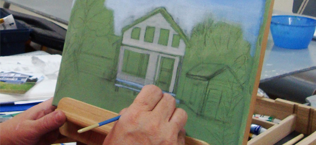 A student painting a house during one of Ginok's art classes.