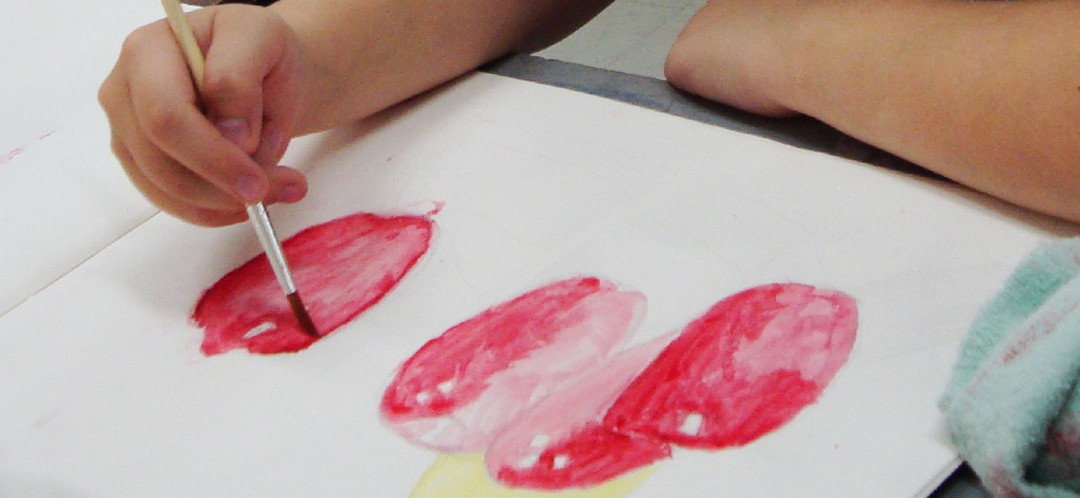 One of Ginok's students painting a water colour of an apple.